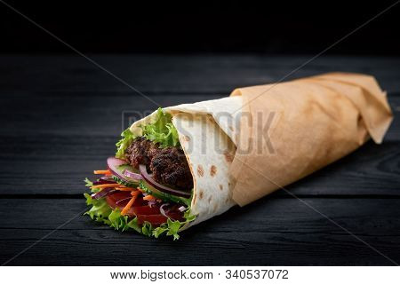 Shawarma Rolled In Lavash, Moist Grilled Meat With Onion, Herbs And Vegetables On Wooden Black Backg