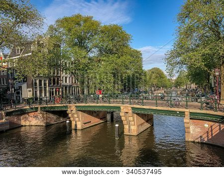 Bicycles On A Bridge Spanning A Canal In Amsterdam