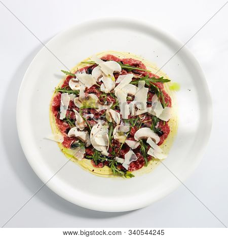 Beef carpaccio with mushrooms, parmesan, fresh arugula and fragrant oil on white restaurant plate isolated.Thin slices of raw veal or venison meat seasoned with vinegar topview