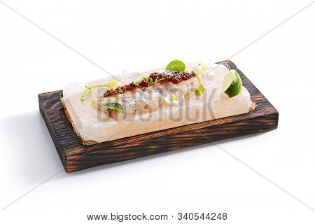 Sea perch ceviche or redfish cebiche on wood restaurant plate isolated. Raw rockfish fillet marinated in lime juice with spicy sauce, edible flowers and greens side view