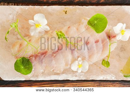 Sea perch ceviche or redfish cebiche on wood restaurant plate isolated. Macro photo of raw rockfish fillet marinated in lime juice with spicy sauce, edible flowers and greens top view