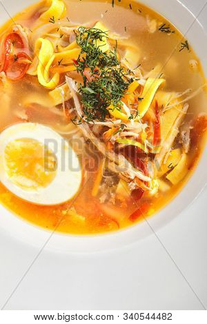 Chicken soup with tagliatelle pasta, eggs and fresh herbs isolated on white background top view. Delicious restaurant clear bouillon with poultry meat, vegetables and spices, view from above
