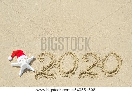 2020 Year Background With Starfish In The Santa Hat On The Sandy Beach