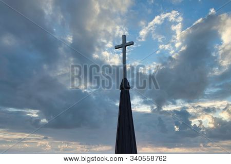 Cross Up On The Top Of Church Steeple Against Cloudy Sky In Background