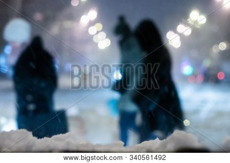 Defocused Photo Of Snow Storm Excessive Precipitation On Winter Street Through Windshield With Peopl