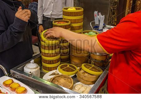 Chinese Waitress Serving Dimsum In Bamboo Steamer Boxes In Restaurant