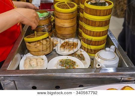 Chinese Waitress Catering Dimsum In Bamboo Steamer Box In Restaurant