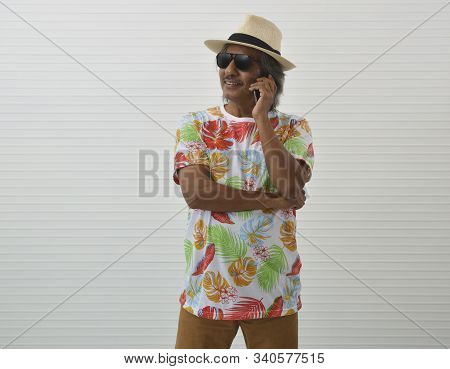 Happy Elderly Traveler Asian Man Wearing Summer Shirt, Straw Hat And Sunglasses Talking With Smart M
