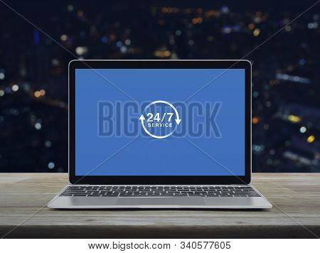 24 Hours Service Flat Icon With Modern Laptop Computer On Wooden Table Over Blur Colorful Night Ligh