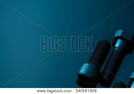 Metal Bolts On Blue Background. Hardware Tools. Closeup Hex Head Bolt And Socket Cap Bolt With Copy