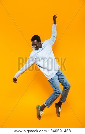 Full length image of happy african american guy in streetwear hoodie smiling and dancing isolated over yellow background