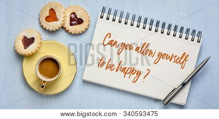 Can you allow yourself to be happy? Inspirational question in a sketchbook with a cup of coffee and heart biscuits. Happinees and positivity concept.