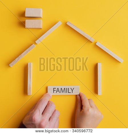 Child And Son Placing A Wooden Peg With Family Sign On It In A House Made Of Wooden Blocks In A Conc