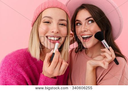 Image of two joyful women wearing girlish clothes smiling and applying makeup with cosmetics isolated over pink background