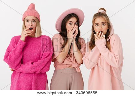 Image of three scared girls wearing pink clothes expressing fright and covering their mouthes isolated over white background