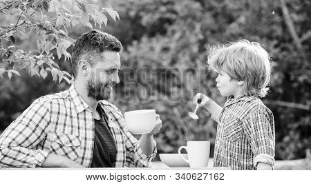 Dad And Cute Toddler Boy Having Lunch Outdoors. Child Care. Feeding Son Natural Foods. Feed In Right