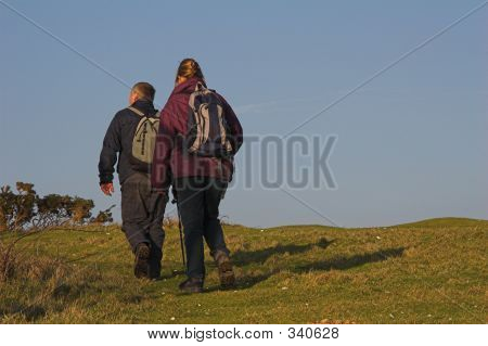 A Couple Hiking Across The Countryside