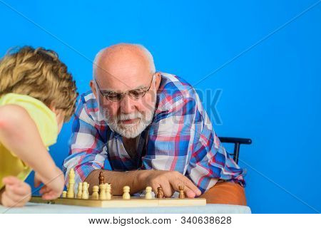 Grandpa Teaching His Grandson To Play Chess. Little Boy Playing Chess With Grandfather At Home. Gran