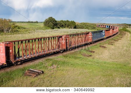 Train Of Empty Lumber Cars Rolling Through Prairie Landscape Under Stormy Skies