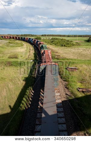 Overhead View Of Train Of Empty Lumber Cars Rolling Through Prairie Landscape Under Stormy Skies
