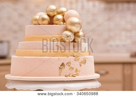 Tiered Birthday Cake On White Plate. Wedding Cake Decorated With Golden Balls And Elements. Luxury C