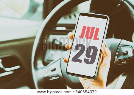 July 29th. Day 29 Of Month, Calendar Date. Month And Day Placed On A Smartphone Screen In Womans Han