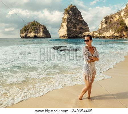 Woman walking on a beach at Diamond Bay, Nusa Penida island, Indonesia