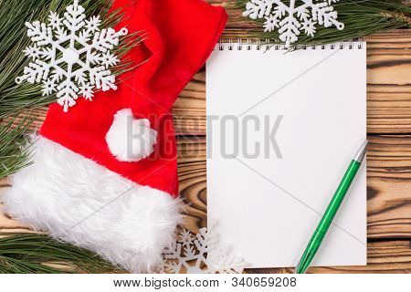 Christmas Background With Blank Notebook, Pine Branches, Santa Hat And Christmas Toys On Wooden Tabl