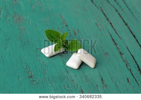 Group Of White Cubes Of Mint Chewing Gums With Fresh Peppermint Leaves On Light Green Wooden Backgro