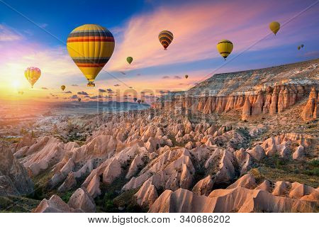 Hot Air Balloons And Red Valley  At Sunset In Goreme, Cappadocia In Turkey.
