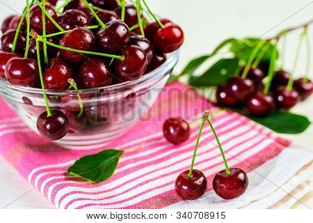 Fresh Sour Cherries In Glass Bowl, Dishcloth And Green Leaves On Wooden Table. Fresh Ripe Sour Cherr