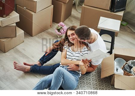 Boyfriend Kisses His Girlfriend. Cheerful Young Couple In Their New Apartment. Conception Of Moving.