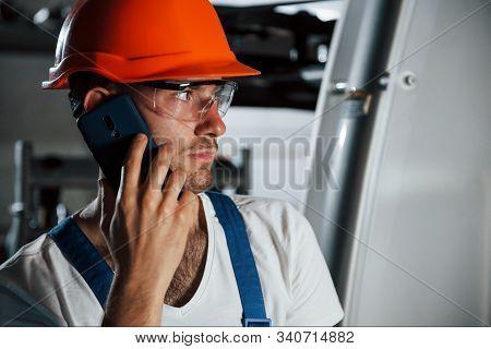 Using Phone. Portrait Of Engineer In Metallurgical Factory In Protective Helmet And Eyewear.