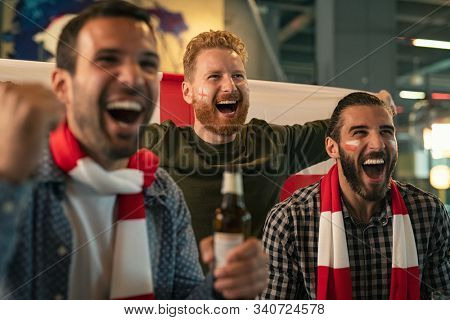 Group of friends watching soccer match in pub. Happy friends drinking beer and cheering together in a bar for a goal. Cheerful soccer fans with painted face having fun watching a sports game on TV.