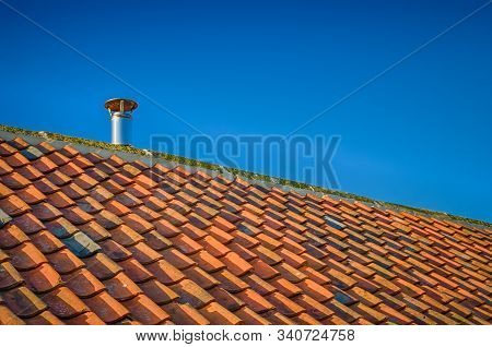 Sloping Tiled Roof Against Blue Sky With Single Metal Flue