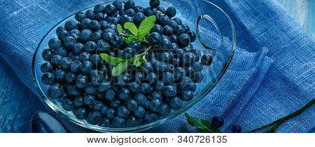 Freshly Blueberries In Glass Bowl. Juicy And Fresh Blueberries With Green Leaves On Blue Wooden Tabl