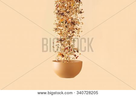 Falling Granola With Candied Fruits And Nuts  To Baige Flying Bowl On Baige Background. Stock Photo