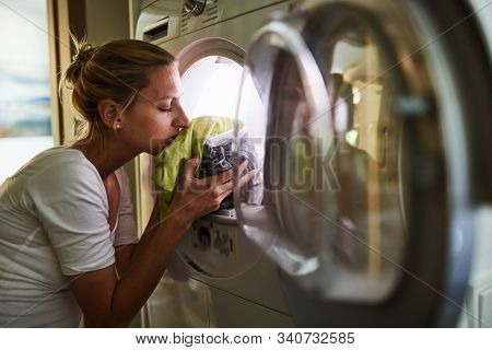 Housewife smells at the clean fresh linen in the clothes dryer at home