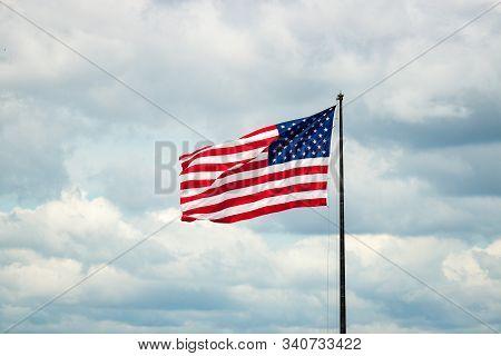 American Flag On Flagpole Against Cloudy Sky