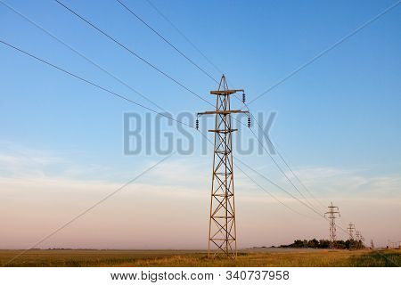 Power Lines On Canadian Prairie At Sunrise In Summer
