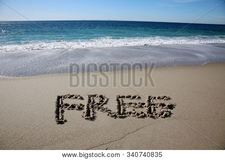 Free written in beach sand. The world FREE written in beach sand with blue pacific ocean water and tide in the background. Laguna Beach California. Vacation spot for world travelers.