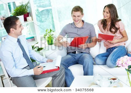Financial agent holding a meeting with a young family at home discussing the terms of the contract