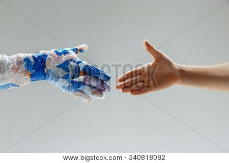 Big Plastic Hand Made Of Garbage Shaking Another Hand On White Studio Background. Polymers Overusing