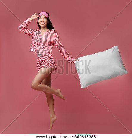 Beautiful Asian Woman With Pillow Jumping On Dusty Rose Background. Bedtime