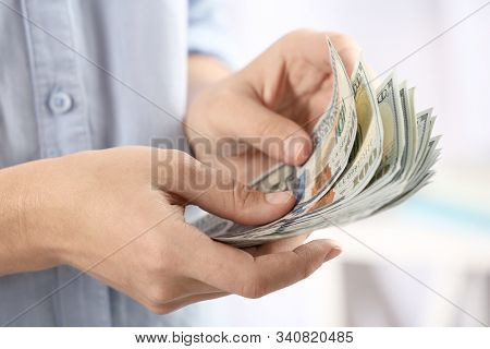 Woman Counting Money On Blurred Background, Closeup