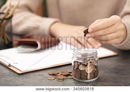Woman Putting Money Into Glass Jar At Table, Closeup