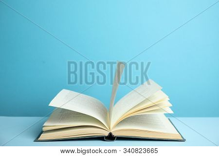 Open Old Hardcover Book On Light Blue Background