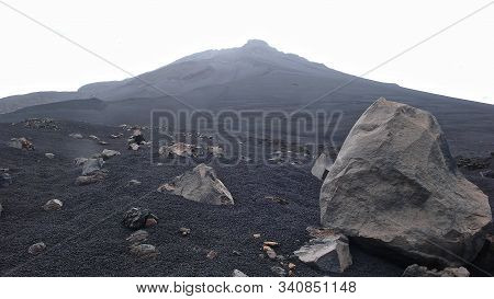 A Stark And Desolate Volcano Creater Landscape With Black Lava Sand And Rocks And Other Craters Behi