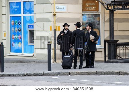 3 Jewish Boys, Hasidic Jews, In Black Clothes And Hats With Suitcases And Luggage Stand On The Stree