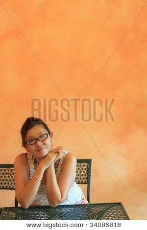 face of asian woman sitting  in front of orange cement wall